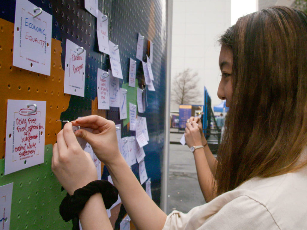 Girl adding to immigration pin-board